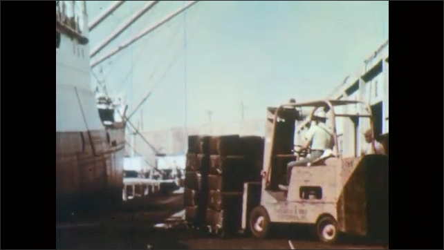 1960s: High angle view of train yard. Ship on water. Crane lifts packages on ship, tilt down to man driving forklift. Men tie ropes to barrels. Hands tie ropes. Man on forklift. Ropes raise barrels.