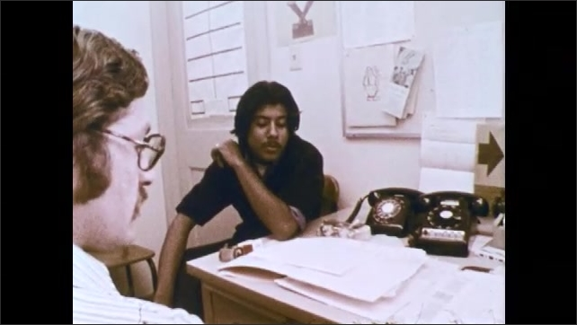 1970s: Man and teenage boy sit at desk and consult papers. Boy reads paper aloud. Teen holds cigarette and looks at man.