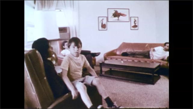 1970s: Woman stokes boys hair on sofa. Teenage boys and children sit on chairs and talk in living room. Teen boy lays on sofa and rests head in woman's lap.