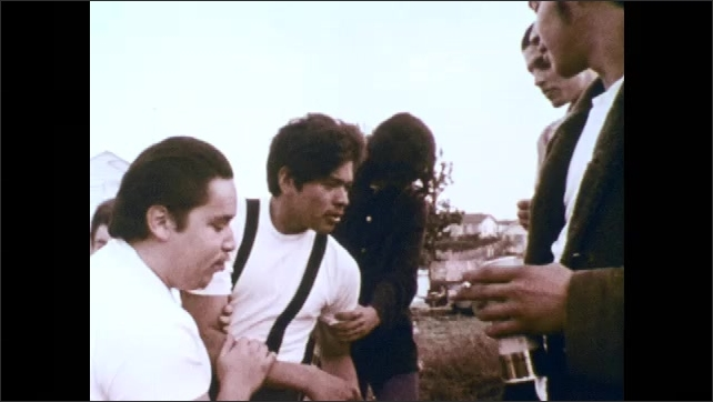 1970s: Boy lies face down on lawn. Teens pick up and brush off boy. Teenage boys laugh and drink. Boys hold up drunk friend.