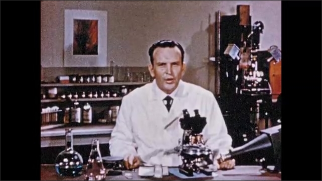 1950s: Man sits at table in front of microscope, talks.