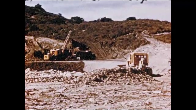 1950s: Large cliff. Truck drives through quarry. Train cars enter tunnel. Mining operation. Man torches brick, heats up spot.