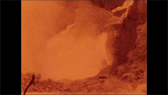 1930s: lava erupts and steam clouds rise from magma pool near craggy rocks in Halemaumau of Hawaii National Park.
