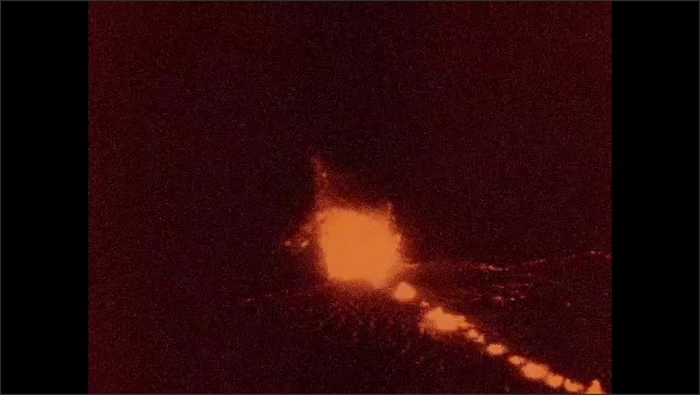 1930s: lava erupts and steam clouds rise from magma pool in Halemaumau of Hawaii National Park at night.