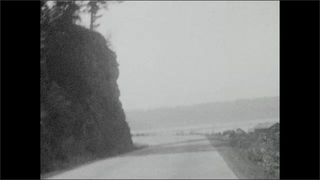 1930s: Trees lined on top of hill. Trees. Driving down road in mountains, by lake.