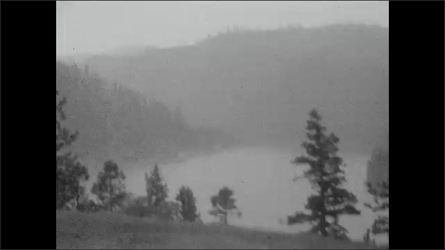 1930s: Hills and trees surrounding lake. Sign for Highway US 10. Lake surrounded by trees and hills.