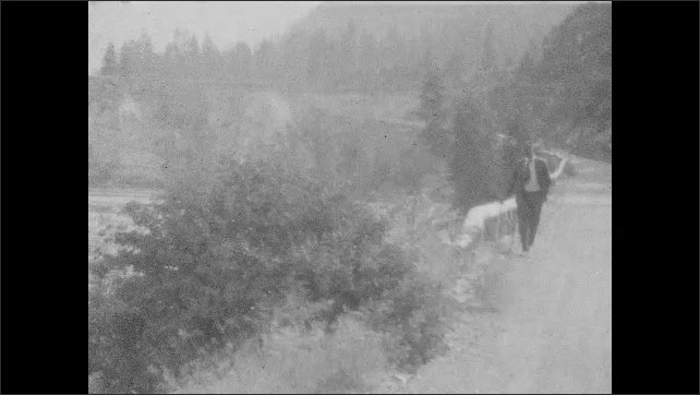 1930s: Road running along hillside. River running through valley. Man on road looks out over river, walks down road.