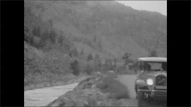 1930s: River runs through valley. Dirt road. River flows by road. Car parked on road. Large, stone arch over road. Moon at night.