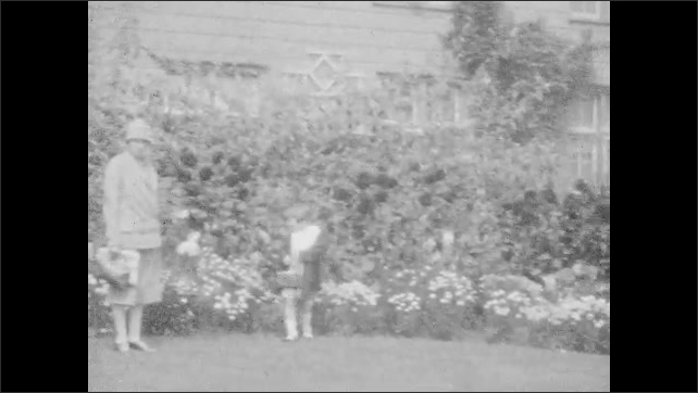 1930s: UNITED STATES: view through trees in valley. Girl sits at table with book. Girl dances. Lady looks at flowers. Lady smiles at camera.