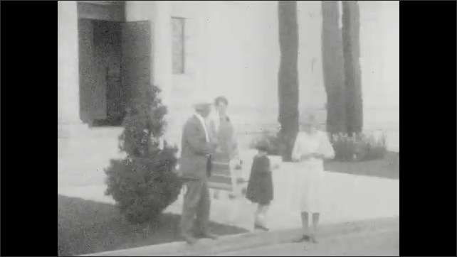 1920s: Sign. Church. Car drives down street. People stand in front of building. Coast. People stand at overlook by ocean.