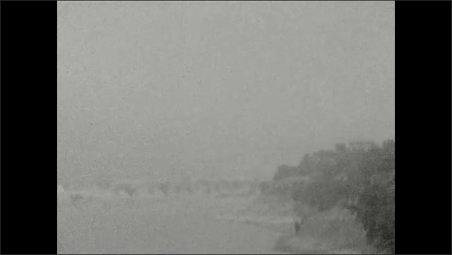 1920s: Bridge, palm trees, lake, mountains. Object travels down mountainside.