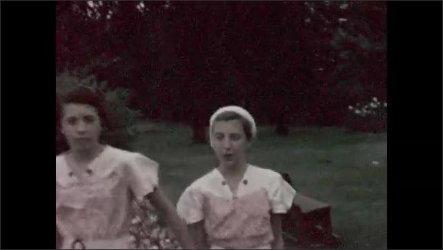 1930s: Girls walk around shrubbery.