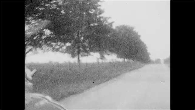1920s: View of river. Tracking shot from car, truck driving on road. Driving on road. View through rear window, women in car. Reflection on man in rearview mirror.