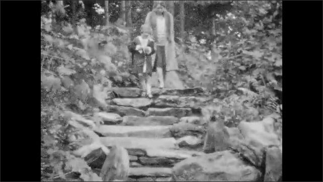 1920s: Woman and girl in gazebo, walk onto path. Woman and girl walk down steps.