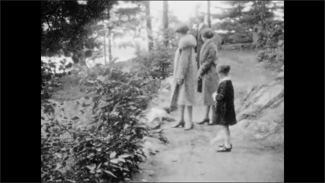 1920s: Boat on water. Close up, nose of boat. People walking on path by water. Women and girl look at water. People walking on path. People walking on path through trees.
