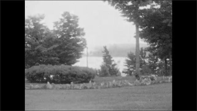 1920s: View of lake through trees. Women on path with girl. Men on lawn in front of building. Long shot, people walk up hill. View of lake. Women on bench, pan across lawn. Men playing bocce ball.