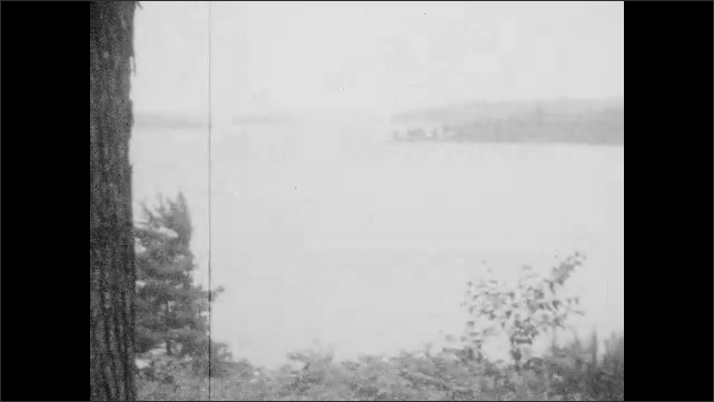 1920s: Girl on path, points to water. View of lake. Views of plants. Man and girl, man holds up life preserver.