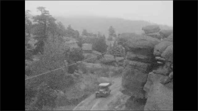 1920s: UNITED STATES: view along road. Rocks by road. Cars drive along track. Family stand on top of hill.