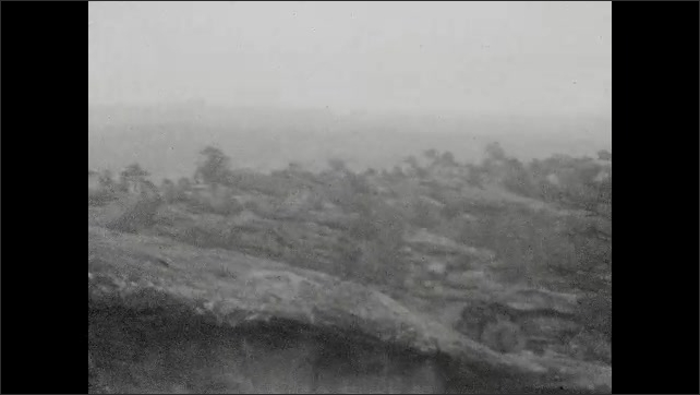 1920s: UNITED STATES: girl holds man's hand. Man and girl walk up rock face. Visit to Balanced Rock.