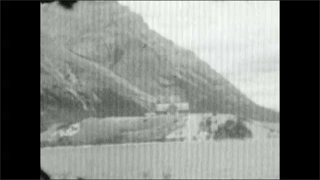 1930s: People on boat.  Mountains.  Lake.  Buildings on shore.