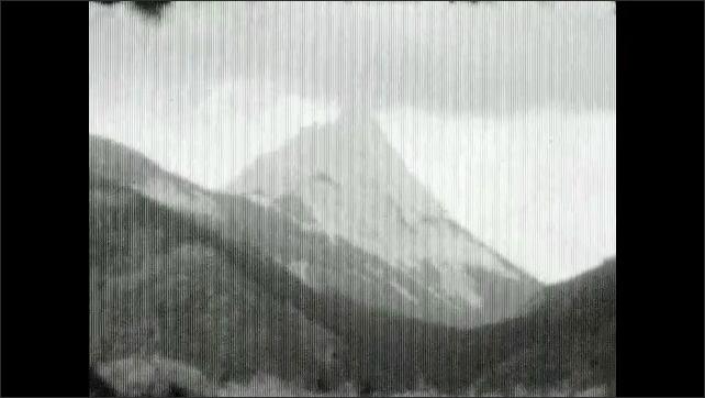 1930s: British flag waves.  Mountains.  Lake.