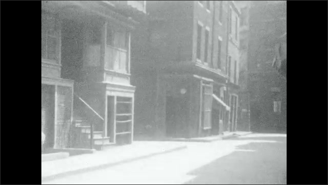 """1930s: Movie lot.  Man sits at table and laughs.  Mother and little girl walk down street.  Man and girl walk out of building labeled """"ROOMING HOUSE."""""""