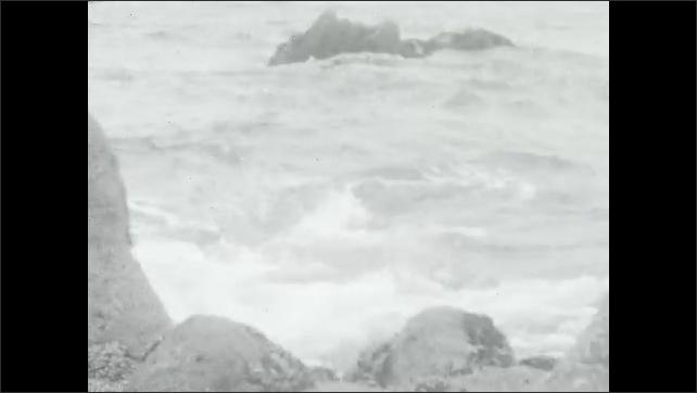 1930s: Waves crash on rocks.