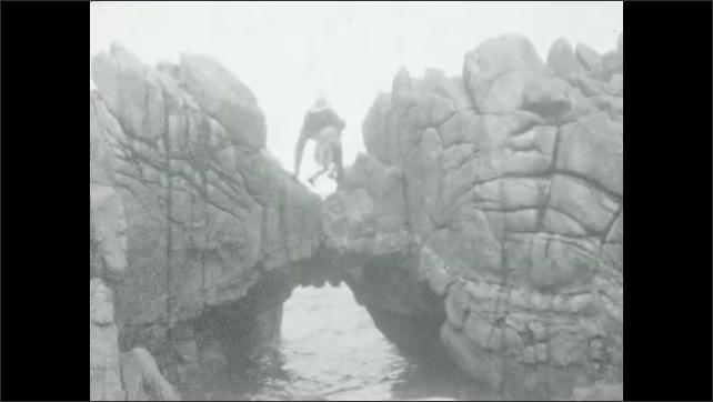 1930s: Beach.  Waves crash on rocks.  Man helps daughter onto rock bridge over water.  Man and girl sit.