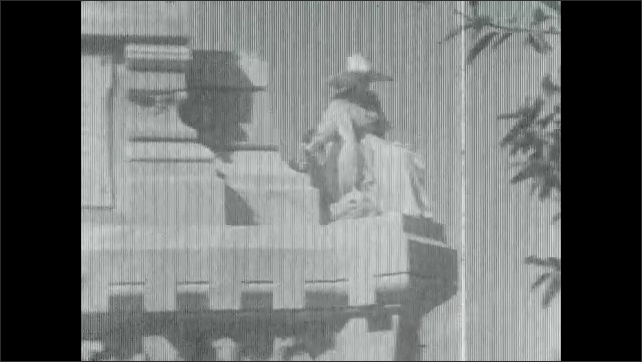 1920s: statue on tall column with human figure and cross on top. woman in hat walks through cemetery with trees, crosses, gravestones, headstones, tombs, crypts and hills.