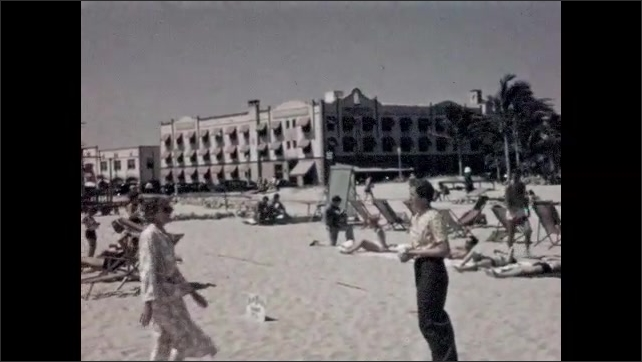 1930s: Man lays on the beach. Woman stands on the beach in front of a beach bar, she walks away. Woman walks on the beach and looks at woman who touches a sign on the sand, buildings in background.