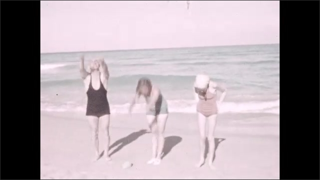 1930s: Two women exercise on the beach. Women and man exercise on the beach, they move their arms up and down to their feet, sea in background. Face of two women who look at mirror and smile.