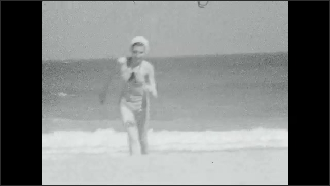 1930s: A woman wears a bikini and runs on the beach, the ocean is in the background, she smiles while she runs.