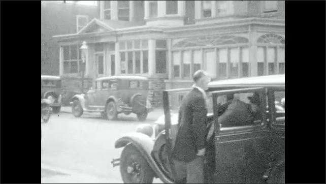1920s: UNITED STATES: people greet each other in street. Car arrives at building. Bride and father arrive for wedding. Families shake hands and kiss.