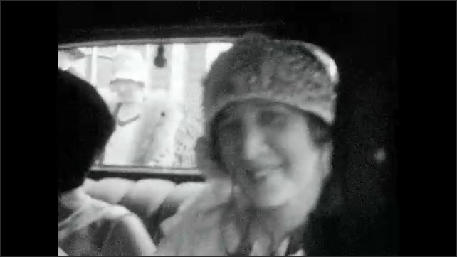 1920s: UNITED STATES: families congratulate each other at wedding. Bride in car. Bride smiles at camera. People at wedding