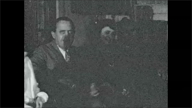 1920s: UNITED STATES: people sit and look at camera. Man smiles at camera. People sit in room at house. Girl sits by man