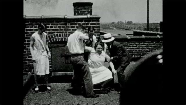 1930s: Men pull women onto rooftop.