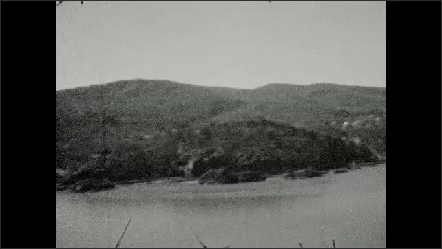1930s: Women looks into opening on roof. View of mountains across Delaware River.