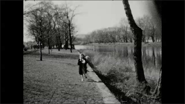 1930s: Children running near river.