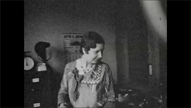 1930s: Women sitting at desks talk to each other. Woman walks in and puts cash away.