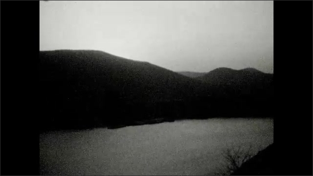 1930s: Panoramic view of mountains across river.