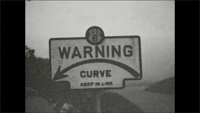1930s: Curve warning sign by road. Man chewing on sidewalk.