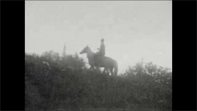 1930s: UNITED STATES: trip on horses. Lady rides horse on excursion. People ride horses in mountains