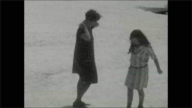 1930s: UNITED STATES: girl slides down snow slope. Visit to glacier.