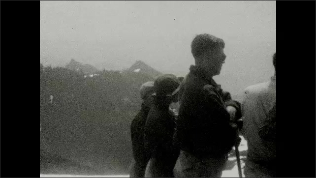 1930s: UNITED STATES: tourists on excursion across glacier. Visitors enjoy view from mountains. Danger Snow bridges are very unsafe. Do not cross them sign.