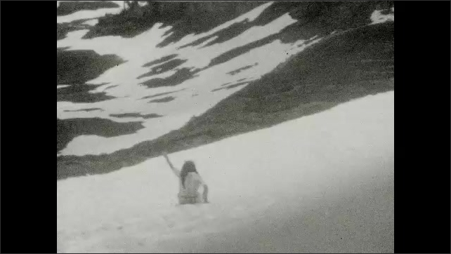 1930s: UNITED STATES: girl sits in snow. Girl slides down snow slope. Water runs down mountain slope