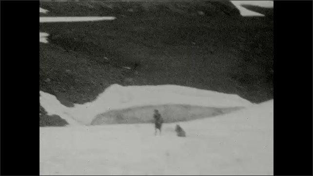 1930s: UNITED STATES: hikers cross glacier. Girls in snow on mountain. Girls slip on slope.