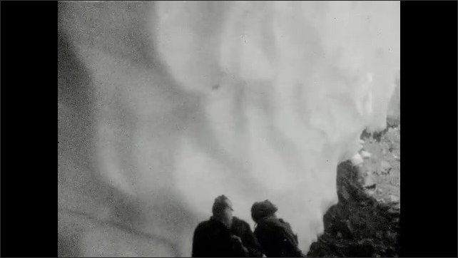 1930s: UNITED STATES: view through ice cave. Water runs down ice cave. Interior of ice cave. Hikers emerge from ice cave