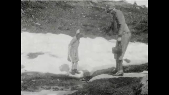 1930s: UNITED STATES: lady and girl walk across snow. Lady and girl walk across river in mountains