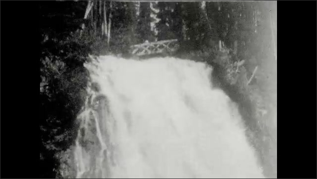 1930s: UNITED STATES: Narada Falls sign. Elevation 4572 ft. sign. Lady and girl walk along mountain path. Longmire sign. Waterfall in mountains.
