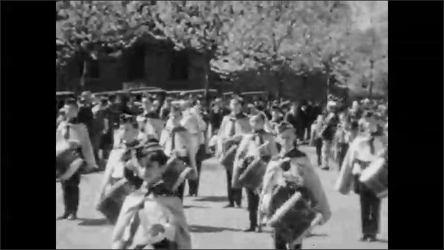 1930s: Children parade down street, play drums. Men parade down the street in military uniforms. Men parade down the street, play bagpipes.